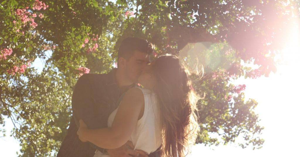 man kissing woman under a tree