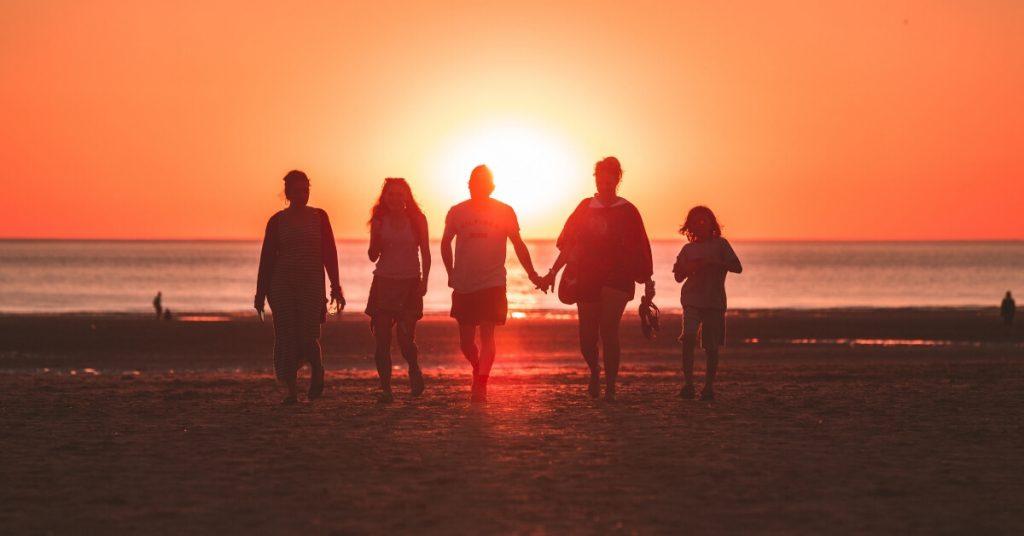 family walking at the beach at sunset