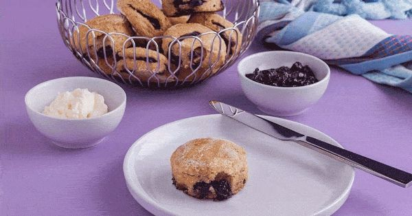 photo shows a blueberry scone on a plate next to some cream