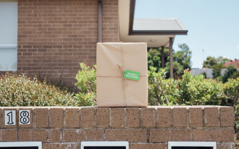 wrapped gift siting on a brick wall